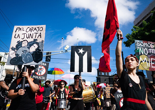 """Image of a street protest, three femmes stand in the foreground all wearing black: the light skinned femme on the right holds up a red flag; in the middle of the image a light brown skinned femme holds up a painted sign with the black and white Puerto Rican resistance flag; and a light brown skinned femme on the left holds up a painted sign that says """"Pa'l Carajo La Junta"""" (Fuck the Fiscal Control Board). Behind these three figures many protestors hold up signs and colorful umbrellas. Three Papel Machete band members play the drums in the background. The sky is bright blue and there are a few clouds in the sky."""